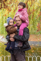 Father carrying son and daughter piggybacks