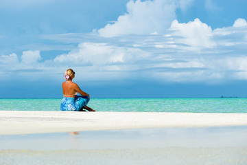 Blonde woman sitting on white sand beach, looking at open sea.Copy space