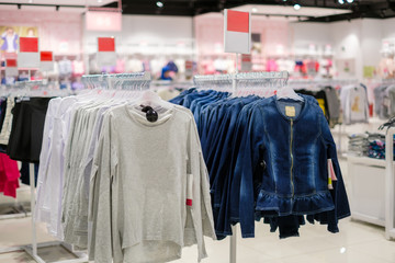 Variety of long sleeve and jeans jackets on hangers in kids clothes store