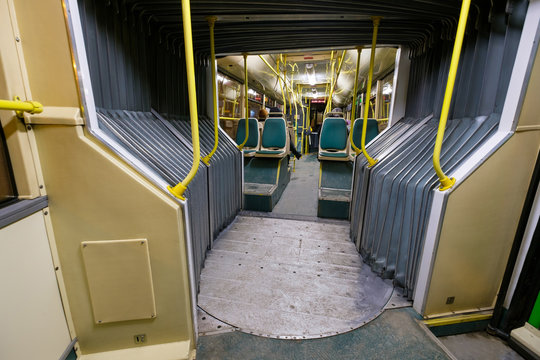 Interior of modern city   articulated bus back part with joint wide angle shot in winter night makes turn