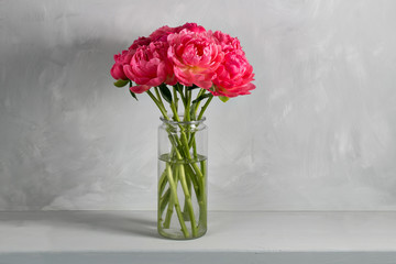 Bouquet of fresh coral peony flowers in glass vase on wood table and gray background. Grade of flowers CoralSharm