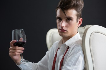 Androgynous man holding wine glass against black background