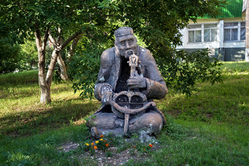 Shabby sculpture of an old musician with a Kazakh national musical instrument in his hands. Petropavl, Kazakhstan.