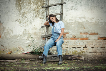 Beautiful young woman is sitting on the ladder leaning on the old rustic wall. Copy Space