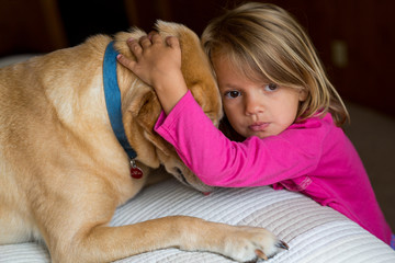 Young child hugging dog