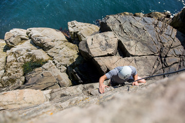Looking down at  climber on rock face