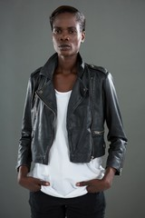 Androgynous man in black jacket posing against grey background