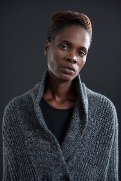 Androgynous person in sweater against grey background