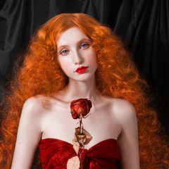 A woman with red hair in a red fitting long dress with dry rose in hand on black background. Red-haired girl with pale skin and blue eyes with a bright unusual appearance. Pin-up woman