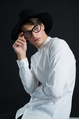 Androgynous man in hat posing with spectacles