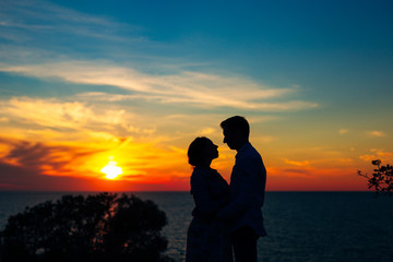 Silhouette of a newlywed couple on the background of the setting sun on the sea in Montenegro.