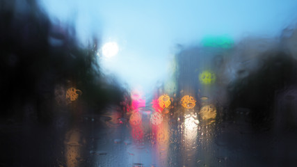 Rain drops on the car glass with traffic light and vintage filter blurred background
