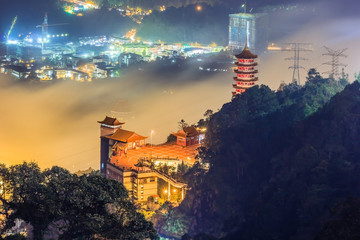 Chin Swee Cave Temple in Genting Highlands at dusk overlooking from viewpoint of Theme park hotel in the background