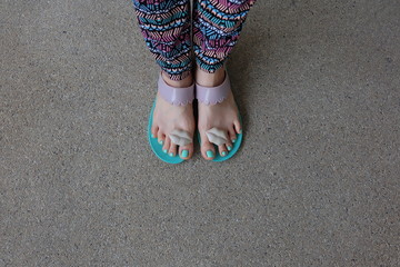 A woman walking on floor, A woman with Sandals and jeans walking alone on floor great for any use.