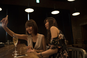 Two ladies are shooting on the smartphone at the bar