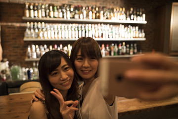 Two women are taking pictures at the bar