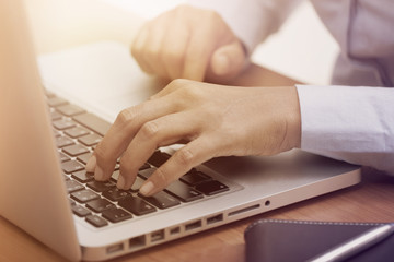 Close up of female hands typing on laptop keyboard at the desk.