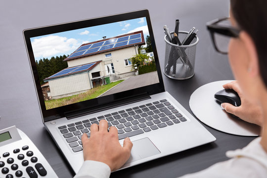 Businesswoman Looking At House On Laptop