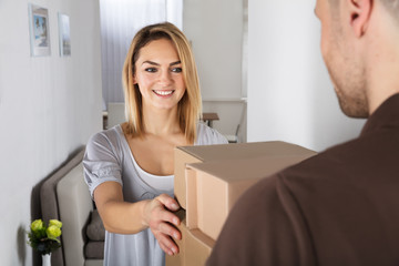 Delivery Man Giving Parcel Box To Young Woman