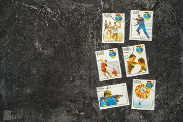 set of randomly lying postage stamps printed in Cuba shows athletes and various sports, devoted to 4 Spartakiad,  series, circa 1977, on a dark black cement background