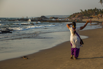 GOA, INDIA - MARCH 4: Happy indian woman is walking at Little Vagator Beach on March 4, 2017, Goa, India