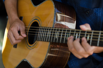 .A young boy sitting acoustic guitar happily.