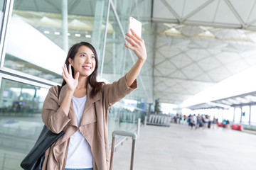 Woman making video call with cellphone in airport