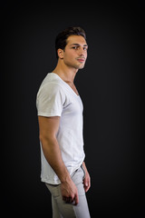 Brown eyed, black haired latin man standing in studio, looking at camera, isolated on black background, profile view