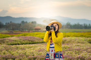 Asian woman photographer is enjoy travel at flower field.