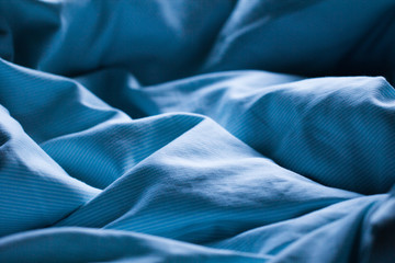Gently sleeping blue bed sheet in soft morning or evening romantic sunlight as beautiful textile sleep relaxation decorative background