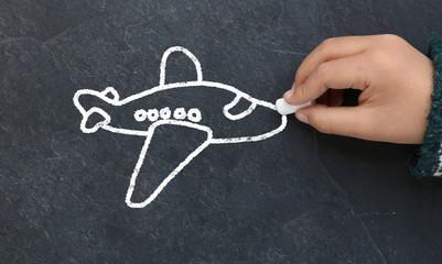 Enfant dessinant un avion sur une ardoise