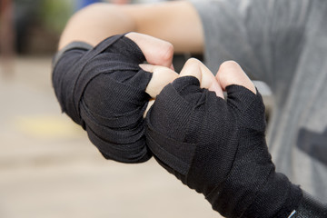 Woman is wrapping hands with black boxing wraps