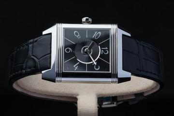Luxury ancient wristwatch with black leather again dark background