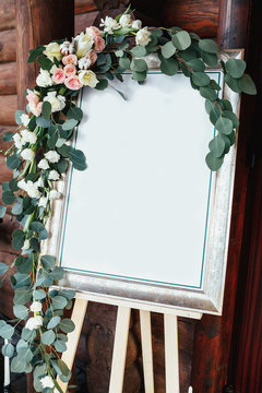 White picture decorated with greenery and roses