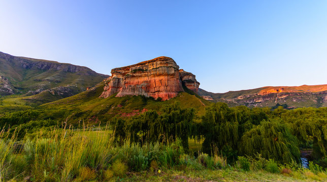 South Africa Drakensberge Golden Gate national park landscape - impressive scenic panoramic nature with red rock landmark, blue sky,trees,sunset, intense colors ,grass