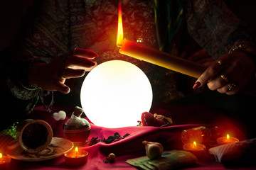 Fortune teller woman holding candle above crystal ball