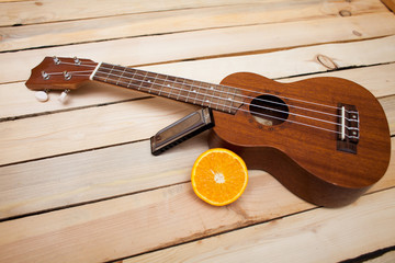 Hawaiian four-stringed ukulele guitar with sliced juicy orange oranges and an iron lip accordion on wooden background