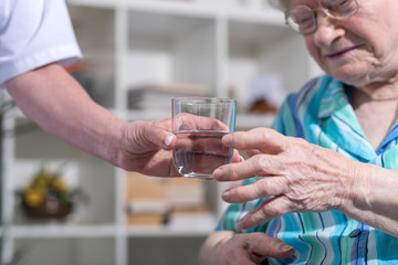 Nurse giving glass of water to senior woman