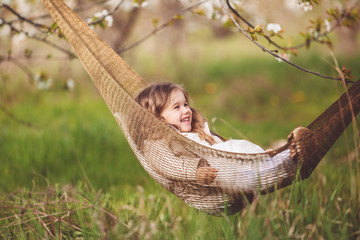 Child girl is resting in hammock in cherry garden