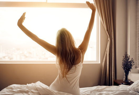 Young woman wake up in bedroom.