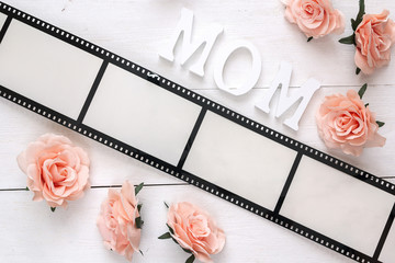 Background with a frame in the form of a film, pink roses and mothers day message on white wooden table.