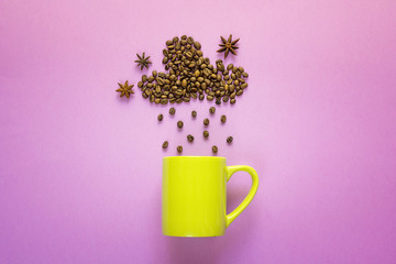 Coffee beans in shape of rainy cloud with anise stars and green mug on purplebackground. Space for text or design.