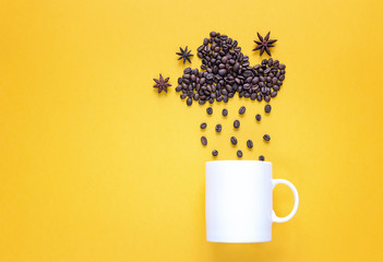 White mug with coffee beans in shape of rainy cloud and anise stars on yellow background.