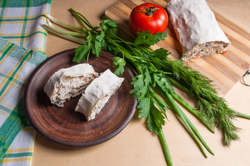 Two pieces of pita bread or lavash roll with cottage cheese or curd, chicken, tomatoes and herbs - dill, onion, parsley on brown clay plate..