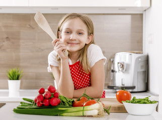 Happy little girl cooking in the kitchen with vegetables
