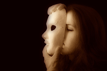 Beautiful brunette girl holding a theatrical mask in white gloves