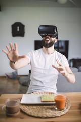 Man having breakfast wearing virtual reality glasses