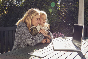 Mother with daughter at garden table looking at laptop