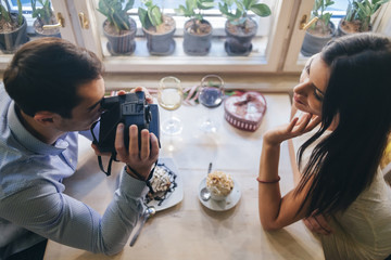 Young couple taking instant photos, top view