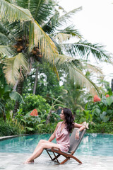 Fashion photo of beautiful tanned woman with brown hair in elegant pink dress relaxing beside a swimming pool